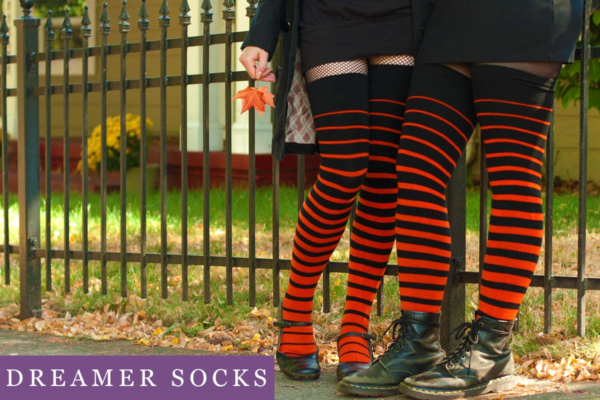 two models wearing orange and white striped thigh highs standing side by side in front of a wrought iron fence, one model holds an orange leaf.