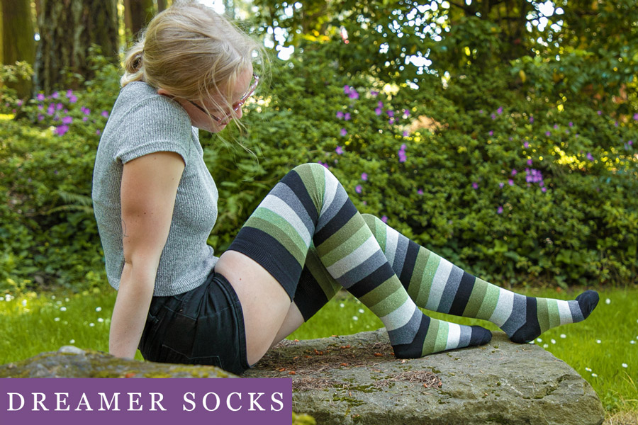 A blonde model is sitting on a boulder wearing long cotton thigh highs in black, greens, and grey stripes.