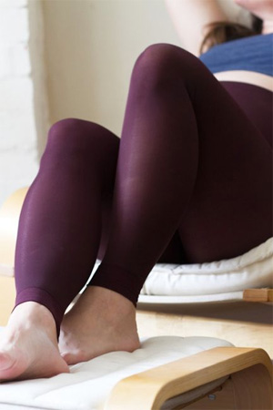 image of a pregnant person lounging back comfortably, wearing dark red leggings