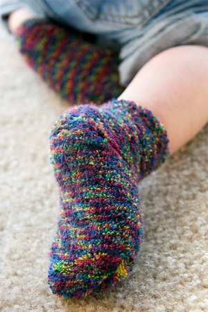 close up shot of tiny baby feet wearing multi-coloured terry socks, as the baby crawls away