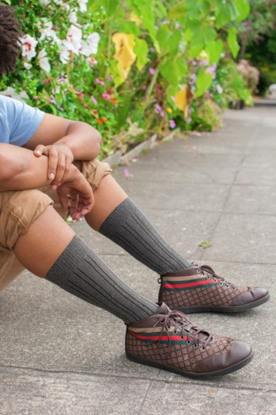 A model with warm, light brown skin sits on the sidewalk, arms leaning on their knees. They're wearing midcalf grey striped dress socks and rad sneakers.