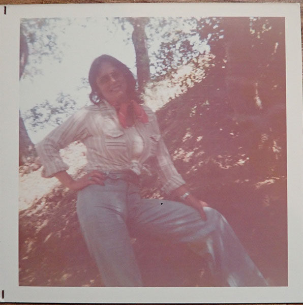 A scanned Polaroid image of a woman standing in a forest, one hand posed on cocked hip, the other bracing against her knee. She wears a jaunty red scarf tied at her neck and a striped button shirt tied at the waist, open over a white undershirt. Her jeans have the high waist and full leg of true 1970s pants.