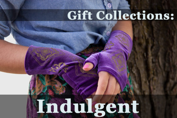 """Image of someone wearing beautiful purple velvet wrist warmers, which look lovely next to a floral skirt. The text over the image reads """"Gift Collections: Indulgent"""""""