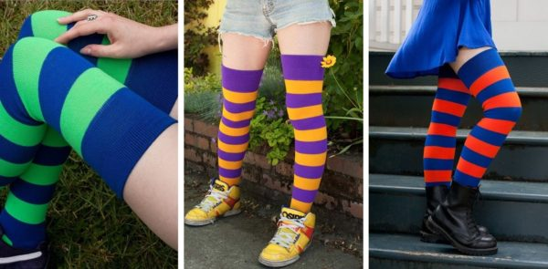 Three images side by side, of models wearing brightly striped thigh highs. Image on the right is shot from above, showing only the model's legs, which are crossed at the ankle, wearing green and blue striped thigh highs. In the center, model is facing the camera at a ¾ angle, wearing purple and gold striped socks with bulky yellow sneakers and denim shorts. On the right, model is facing to the right, shot from the waist down, wearing royal blue and orange striped thigh highs with a matching blue skirt.