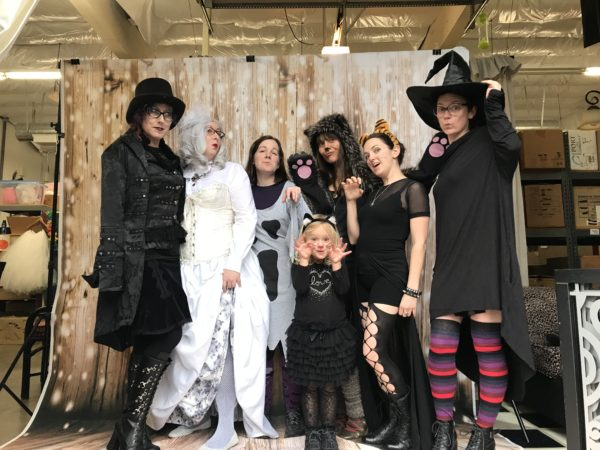 Group shot of people in costumes, taken inside a warehouse, in front of a film set.