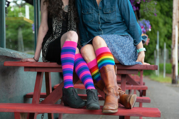 Two people sitting next to each other on a picnic table. One is wearing knee socks striped purple, blue, pink, and the other is wearing knee socks striped in a classic rainbow with pink.