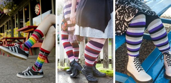 Three images side by side. On the left someone is wearing rainbow socks with brown and black stripes, made to look like an old fashioned library card. In the middle two people are standing back to back, wearing matching socks striped like the lesbian pride flag. On the right someone is sitting on a blue picnic table, wearing over the knee socks striped like the asexual pride flag.