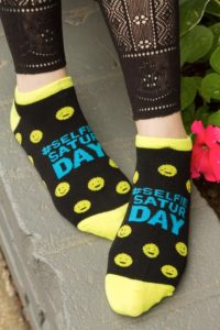 A person wearing footies with smiley faces and #selfiesaturday printed on the sock.
