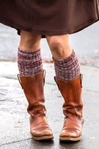 A person wearing dark red and cream marled knee highs with light brown cowboy boots and a brown skirt.