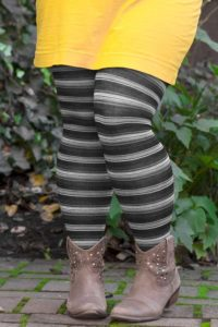 A person wearing striped grey wool tights with ankle boots and a yellow skirt.