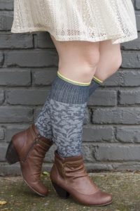 A person wearing damask textured compression knee highs with brown ankle boots and a cream skirt.