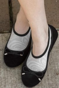 A person wearing grey no-show socks with a swirly pattern, in black flats.